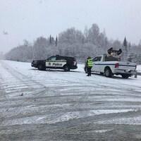 un véhicule de la SQ et de Transports Québec sur une route enneigée