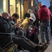 Des clients attendent sur des chaises pliantes sur le trottoir.
