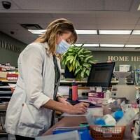 Stacy Jardine prenant des notes à son comptoir de pharmacie.