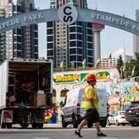 Un travailleur marche sur le site du Stampede. Derrière lui, on voit des camions et des kiosques en voie d'installation pour le festival.