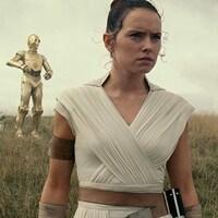 Rey porte une tenue blanche et les cheveux relevés.