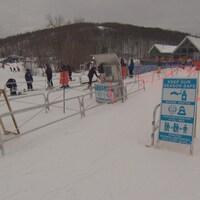 Des pancartes rappelant les mesures d'hygiènes en temps de pandémie au bas d'une pente de ski.