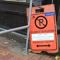Une affiche indique que le stationnement est interdit entre 16h00 et 21h00.