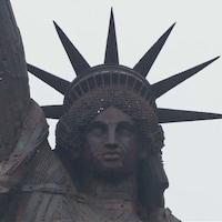 Gros plan sur le visage d'une réplique de la statue de la Liberté faite de ferraille.