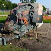 La statue, sans tête, est érendue par terre. Des drapeaux plantés dans le sol rappellent la mémoire des enfants autochtones morts dans les pentionnats.
