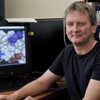 Jörg Stetefeld pose devant un écran qui montre une image prise avec un microscope électronique.