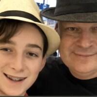 Stéphane Roy et son fils portant chacun un chapeau, sourient à la caméra.