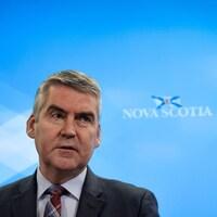 Stephen McNeil devant un fond bleu sur lequel est écrit « Nova Scotia » avec un dessin du drapeau de la Nouvelle-Écosse.