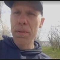 Un homme parle à la caméra.