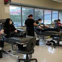 Trois personnes asiatiques donnent du sang dans une clinique de la Société canadienne du sang.
