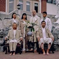 Des modèles d'origine asiatique posent devant une pagode.