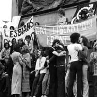 Des gens sont réunis au pied d'une statue. Un homme parle dans un micro. Des couples de même sexe s'embrassent. D'autres tiennent des banderoles revendicatrices.