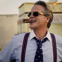 Un homme portant des lunettes de soleil et une chemise fume un cigare en souriant.