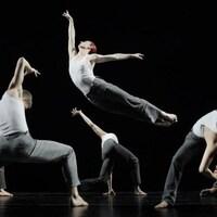 Six danseurs effectuent une chorégraphie de danse contemporaine.