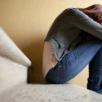 Une femme désespérée est assise dans un escalier. Elle se cache le visage pour pleurer.