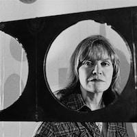 Gros plan du visage de Françoise Sullivan derrière une de ses sculptures.