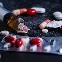 Une seringue, des pilules et de la poudre placés aléatoirement..
