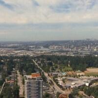 Grand plan de la région de Vancouver pris du haut d'un immeuble de Surrey avec des tours de bureaux, une partie du fleuve Fraser et un quartier résidentiel.