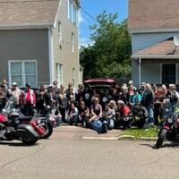 Une trentaine de motocyclistes devant une maison.