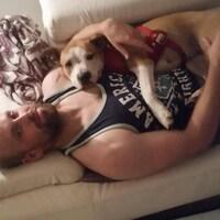 Daniel MacKay est couché sur un canapé avec un chien sur lui.
