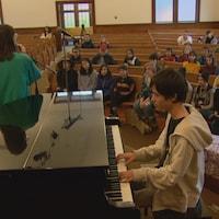 Un pianiste et une chanteuse performent devant public.