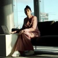 Une femme, tout de rose vêtue, est assise dans un canapé. Devant elle, un ordinateur est posé sur une table. Dehors, il fait beau.