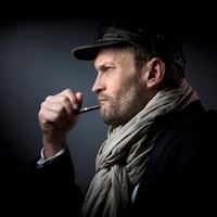 Portrait de Sylvain Tesson de profil, qui a une pipe dans la bouche