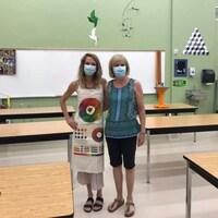 Deux femmes posent ensemble dans une salle de classe d'art.