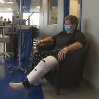 On voit Mme Gunner assise dans une fauteuil à l'hôpital, en entrevue pour la télévision.