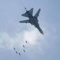 Un avion militaire laissant tomber 6 petites bombes, vu d'en-dessous.