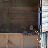 Femmes et enfants quittent le secteur de Baghouz, en Syrie, dans des camions.