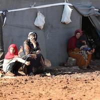 Des femmes et des enfants assis sur des blocs de béton.