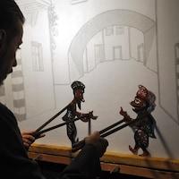 Shadi al-Hallaq contrôlant les marionnettes de Karakoz et Eiwaz, deux personnages emblématiques du théâtre d'ombres syrien.