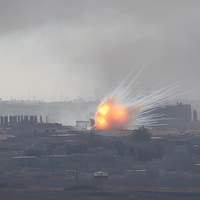Feu et fumée d'une explosion près de bâtiments.