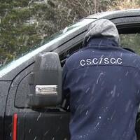 Un employé de Service correctionnel du Canada se tient sur le bord du véhicule de l'employé se rendant au travail.