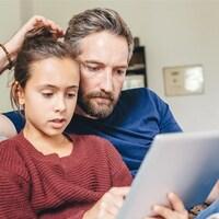 Une fille et son père regardent une tablette.