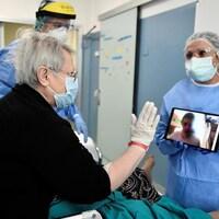 Une patiente dans un lit d'hôpital participe à une vidéoconférence sur une tablette tenue par du personnel hospitalier.