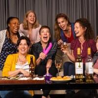 Sept femmes rigolent sur un canapé.