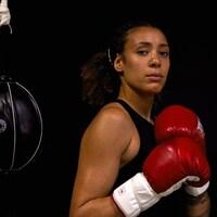 Une femme regarde la caméra avec des gants de boxe.