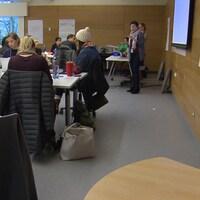 Une trentaine d'étudiants suivent un cours dans une classe de l'université Simon Fraser. La plupart regardent le professeur qui parlent devant le tableau.
