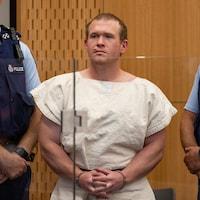 Tarrant, dans un tribunal, entre deux policiers.