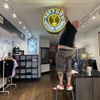 Le directeur d'un salon de tatouage accroche une enseigne dans sa boutique.