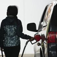 Photo: Radio-Canada\ Ivanoh Demers Une femme remplit sa voiture d'essence à une station-service.