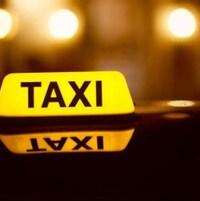 Signe d'un taxi illuminé dans la nuit.