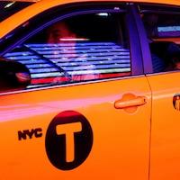 Une femme regarde par la fenêtre d'un taxi jaune.