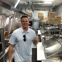 Rob Taylor, souriant dans la cuisine du restaurant, fait un geste d'optimisme en levant son pouce.