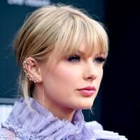 Taylor Swift porte une tenue mauve.