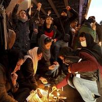 Des gens scandent des slogans, le poing dans les airs, alors que d'autres déposent des bougies par terre.