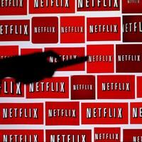 Une main tenant une télécommande devant une série de logos du service Netflix.