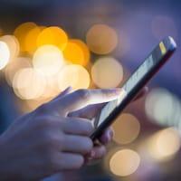 Une femme tient un téléphone mobile dans sa main.
